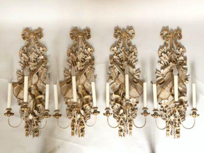 Quatre appliques en bois sculptés aux attributs de musique.